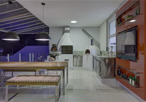 Juliana Buli - Nessa área gourmet, as cadeiras transparentes fazem um contraponto interessante com os bancos e mesa de madeira