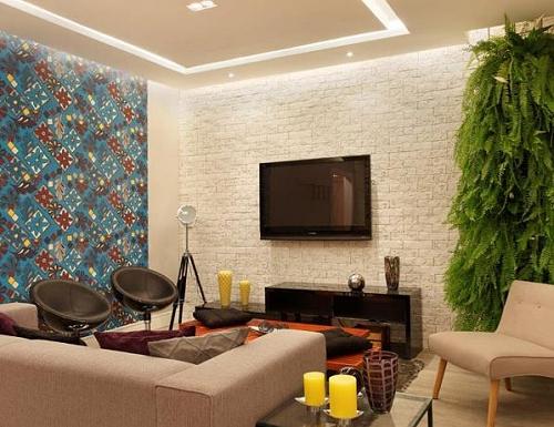 Na sala de TV, uma das paredes é tomada por papel adesivo que lembra